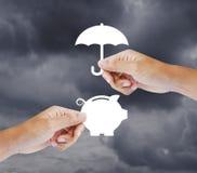 Χέρι που κρατά μια piggy τράπεζα και μια ομπρέλα εγγράφου Στοκ Φωτογραφία
