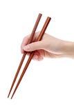 Χέρι που κρατά ξύλινα chopsticks στοκ εικόνες