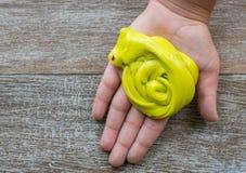 Χέρι που κρατά σπιτικό κίτρινο slime με tinsel στοκ φωτογραφία με δικαίωμα ελεύθερης χρήσης