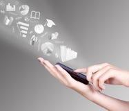 Χέρι που κρατά τα έξυπνα κινητά σύμβολα τηλεφώνων και ανταλλαγής που πετούν μακριά Στοκ φωτογραφία με δικαίωμα ελεύθερης χρήσης