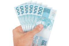 Χέρι που κρατά τα βραζιλιάνα χρήματα στοκ φωτογραφία