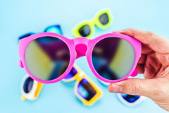 Χέρι που κρατά τα ζωηρά ρόδινα γυαλιά ηλίου με την ομάδα θαμπάδων γυαλιών Στοκ Φωτογραφίες