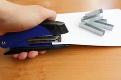 Χέρι που κρατά τα μπλε stapler συρράπτοντας έγγραφα Στοκ Φωτογραφίες