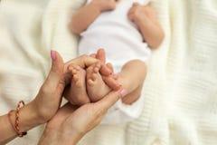 Χέρι που κρατά τα πόδια λίγου μωρού στοκ φωτογραφία