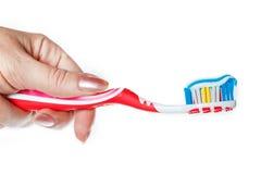 Χέρι που κρατά την κόκκινη οδοντόβουρτσα με την μπλε οδοντόπαστα δύο χρώματος Στοκ εικόνες με δικαίωμα ελεύθερης χρήσης