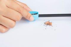 Χέρι που κρατά την μπλε ξύστρα για μολύβια με τα ξέσματα στο άσπρο backgr Στοκ Φωτογραφία