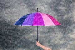 Χέρι που κρατά την πολύχρωμη ομπρέλα κάτω από το σκοτεινό ουρανό με τη βροχή Στοκ εικόνες με δικαίωμα ελεύθερης χρήσης