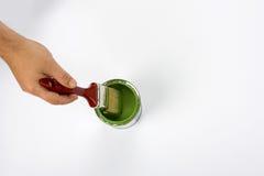 Χέρι που κρατά την πράσινη βούρτσα χρωμάτων Στοκ Φωτογραφίες