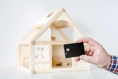 Χέρι που κρατά τη μαύρη πλαστική κάρτα τσιπ Ξύλινο πρότυπο σπιτιών στο υπόβαθρο Μεταφορά πληρωμής καλωδίων Συναλλαγή χρημάτων Cas Στοκ Εικόνες