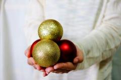 Χέρι που κρατά τη χρυσή και κόκκινη διακόσμηση με το άσπρο πουλόβερ Στοκ Εικόνες