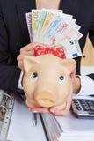 Χέρι που κρατά τη piggy τράπεζα και το ευρώ Στοκ εικόνες με δικαίωμα ελεύθερης χρήσης
