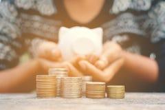 Χέρι που κρατά τη piggy τράπεζα και το νόμισμα στο παλαιό ξύλο Στοκ Εικόνα