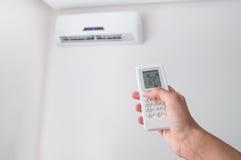 Χέρι που κρατά τον τηλεχειρισμό για το κλιματιστικό μηχάνημα στον άσπρο τοίχο Στοκ Φωτογραφίες