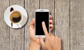 Χέρι που κρατά το άσπρο έξυπνο τηλέφωνο στο ξύλινο τραπεζάκι σαλονιού Στοκ Φωτογραφία