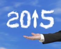 Χέρι που κρατά το άσπρο βέλος του 2015 επάνω στα σύννεφα μορφής με τον ουρανό Στοκ φωτογραφία με δικαίωμα ελεύθερης χρήσης