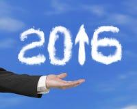 Χέρι που κρατά το άσπρο βέλος του 2016 επάνω στα σύννεφα μορφής με τον ουρανό Στοκ Εικόνα