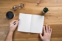 Χέρι που κρατά το άσπρο κενό πρότυπο φύλλων εγγράφου στο ξύλινο υπόβαθρο στοκ φωτογραφία με δικαίωμα ελεύθερης χρήσης