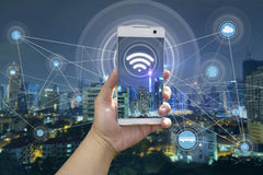 Χέρι που κρατά το άσπρο τηλέφωνο με την πόλη scape στοκ εικόνες με δικαίωμα ελεύθερης χρήσης