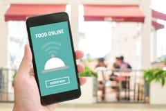 Χέρι που κρατά το έξυπνο τηλέφωνο με τη σε απευθείας σύνδεση συσκευή τροφίμων στην οθόνη Στοκ εικόνες με δικαίωμα ελεύθερης χρήσης