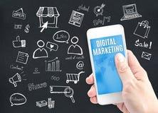 Χέρι που κρατά το έξυπνο τηλέφωνο με την ψηφιακή λέξη μάρκετινγκ και doodles Στοκ φωτογραφία με δικαίωμα ελεύθερης χρήσης
