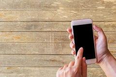 Χέρι που κρατά το έξυπνο τηλέφωνο με το ξύλινο επιτραπέζιο υπόβαθρο στοκ φωτογραφίες