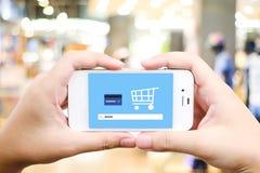 Χέρι που κρατά το έξυπνο τηλέφωνο με το www στο φραγμό αναζήτησης πέρα από το κατάστημα θαμπάδων Στοκ Εικόνες