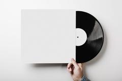 Χέρι που κρατά το βινυλίου πρότυπο λευκωμάτων μουσικής στο λευκό Στοκ εικόνα με δικαίωμα ελεύθερης χρήσης