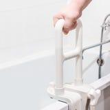 Χέρι που κρατά το κιγκλίδωμα στο λουτρό Στοκ εικόνα με δικαίωμα ελεύθερης χρήσης