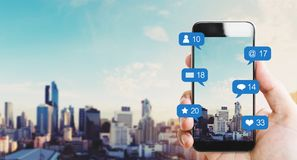 Χέρι που κρατά το κινητό έξυπνο τηλέφωνο, με τα εικονίδια ανακοίνωσης και το υπόβαθρο πόλεων στοκ εικόνες με δικαίωμα ελεύθερης χρήσης