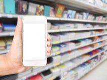 Χέρι που κρατά το κινητό έξυπνο τηλέφωνο στο ράφι στη θαμπάδα καταστημάτων βιβλίων Στοκ Εικόνα