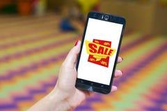 Χέρι που κρατά το κινητό τηλέφωνο με το σημάδι πώλησης στοκ φωτογραφίες με δικαίωμα ελεύθερης χρήσης