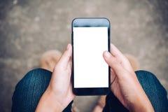 χέρι που κρατά το κινητό τηλέφωνο με την κενή άσπρη οθόνη στο μηρό με στοκ εικόνα