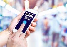 Χέρι που κρατά το κινητό τηλέφωνο με την ψηφιακή λέξη πορτοφολιών με θολωμένος Στοκ φωτογραφίες με δικαίωμα ελεύθερης χρήσης