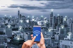 Χέρι που κρατά το κινητό τηλέφωνο με το δίκτυο σύνδεσης δικτύων wifi Στοκ Φωτογραφία