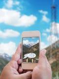 Χέρι που κρατά το κινητό τηλέφωνο με το μεγάλο δορυφόρο Στοκ εικόνα με δικαίωμα ελεύθερης χρήσης