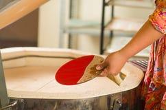 Χέρι που κρατά το κόκκινο και trasnaprent πιάτο με τα συμπαθητικά χρυσά διακοσμητικά λωρίδες σε το Στοκ εικόνες με δικαίωμα ελεύθερης χρήσης