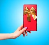 Χέρι που κρατά το κόκκινο δώρο Στοκ Εικόνα