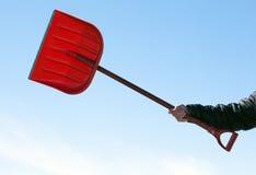 Χέρι που κρατά το κόκκινο snowshovel Στοκ Εικόνα