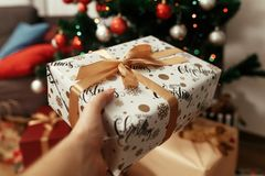 Χέρι που κρατά το μοντέρνο χριστουγεννιάτικο δώρο στο υπόβαθρο του δέντρου Στοκ Φωτογραφία