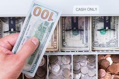 Χέρι που κρατά το λογαριασμό εκατό δολαρίων πέρα από το συρτάρι μετρητών στοκ εικόνα