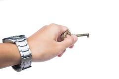 Χέρι που κρατά το παλαιό εκλεκτής ποιότητας χρυσό κλειδί στο άσπρο υπόβαθρο στοκ εικόνες