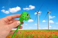 Χέρι που κρατά το πράσινο ηλεκτρικό βούλωμα στους ανεμοστροβίλους υποβάθρου Στοκ φωτογραφία με δικαίωμα ελεύθερης χρήσης