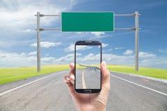 Χέρι που κρατά το smartphone στην οδική καμπύλη με το πράσινο μπλε χλόης Στοκ Εικόνα