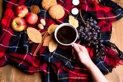 Χέρι που κρατά φλιτζανιών του καφέ της Apple μπισκότων κανέλας σταφυλιών την ξύλινη υποβάθρου κορυφή VI έννοιας τρόπου ζωής φθινο Στοκ Φωτογραφία