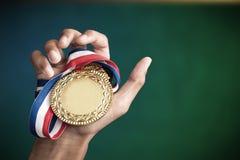Χέρι που κρατά ψηλά ένα χρυσό μετάλλιο Στοκ Εικόνες