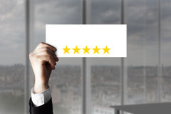 Χέρι που κρατά ψηλά το μικρό σημάδι πέντε αστέρια εκτίμησης Στοκ φωτογραφία με δικαίωμα ελεύθερης χρήσης