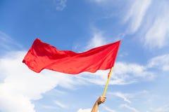 Χέρι που κυματίζει μια κόκκινη σημαία με το υπόβαθρο μπλε ουρανού Στοκ φωτογραφία με δικαίωμα ελεύθερης χρήσης