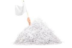 Χέρι που κυματίζει την άσπρη σημαία από το σωρό του τεμαχισμένου εγγράφου Στοκ εικόνα με δικαίωμα ελεύθερης χρήσης