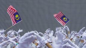 Χέρι που κυματίζει τη σημαία της Μαλαισίας γνωστή επίσης ως Jalur Gemilang Στοκ Εικόνες