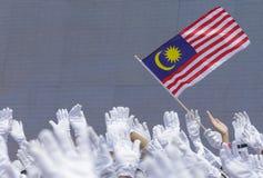 Χέρι που κυματίζει τη σημαία της Μαλαισίας γνωστή επίσης ως Jalur Gemilang Στοκ Φωτογραφία